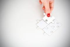Frauenhand, die das rechte Stück des Puzzlespiels Geschäftsvernetzungskonzept vorschlagend passt Stockbild