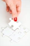 Frauenhand, die das rechte Stück des Puzzlespiels Geschäftsvernetzungskonzept vorschlagend passt Stockfoto