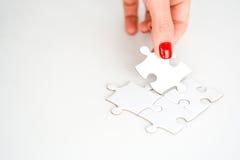 Frauenhand, die das rechte Stück des Puzzlespiels Geschäftsvernetzungskonzept vorschlagend passt Stockfotografie