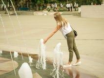 Frauenhand, die das Wasser im Stadtbrunnen berührt Lizenzfreies Stockbild