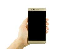 Frauenhand, die den goldenen Smartphone auf weißem Hintergrund hält Lizenzfreie Stockfotos