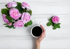 Frauenhand, die den Tasse Kaffee, umgeben mit rosafarbenen Blumen gegen weißen Weinleseholztisch hält Flache Lage, Draufsicht lizenzfreies stockbild