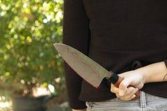 Frauenhand, die ein blutiges Messer auf einem schwarzen Hintergrund, Sozialgewalttätigkeits-Halloween-Konzept, Foto des diabolisc lizenzfreie stockfotografie