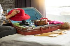 Frauenhand, die ein Gepäck für eine neue Reise und eine Reise für a verpackt stockfoto