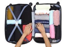 Frauenhand, die ein Gepäck für eine neue Reise verpackt stockfoto