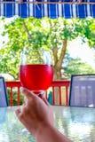 Frauenhand, die ein Glas Rotwein hält Lizenzfreies Stockfoto