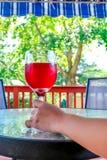 Frauenhand, die ein Glas Rotwein hält Lizenzfreie Stockfotos