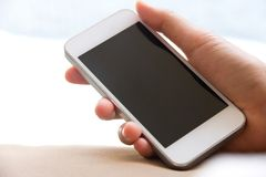Frauenhand, die ein intelligentes Telefon hält Stockbild