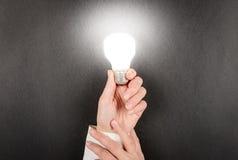 Frauenhand, die eine Glühlampebirne hält Lizenzfreies Stockbild
