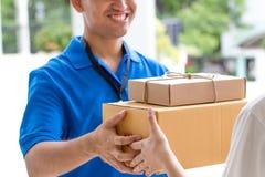 Frauenhand, die eine Lieferung von Kästen vom Lieferboteen annimmt Lizenzfreies Stockfoto
