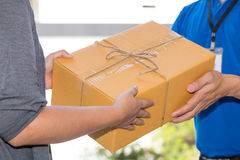 Frauenhand, die eine Lieferung von Kästen vom Lieferboteen annimmt Lizenzfreie Stockfotografie