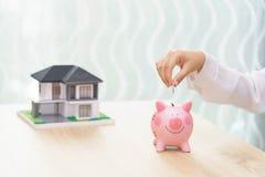 Frauenhand, die eine Münze in ein Sparschwein auf hölzernem Schreibtisch - SAV setzt lizenzfreie stockbilder
