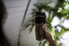 Frauenhand, die eine Schokoladenerschütterung und -plätzchen auf einem transparenten Glas mit eingeborenem Entwurf hält lizenzfreie stockfotos