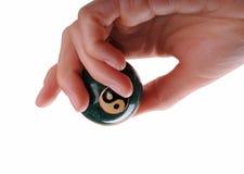 Frauenhand, die einen Ball mit Ying und Yang-Symbolen hält Lizenzfreies Stockbild