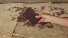 Frauenhand, die einen Block der handgemachten Schokolade mit trockenen Kakaobohnen hält Lizenzfreies Stockfoto