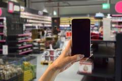 Frauenhand, die einen Smartphone während auf dem Speichereinkaufen hält Lizenzfreies Stockfoto