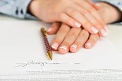 Frauenhand, die einen Vertrag unterzeichnet lizenzfreies stockbild