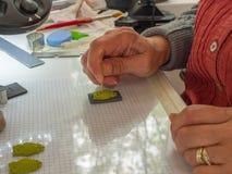 Frauenhand, die Eulenknopf vom Polymerlehm herstellt Hobby, Handwerkshintergrund Stockbild