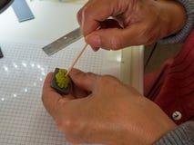 Frauenhand, die Eulenknopf vom Polymerlehm herstellt Hobby, Handwerkshintergrund Lizenzfreie Stockfotos