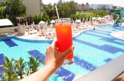 Frauenhand, die Glas mit einem überlagerten Cocktail auf Poolhintergrund hält Sommerreise, Ferien, alles einschließliche Konzept lizenzfreie stockfotos