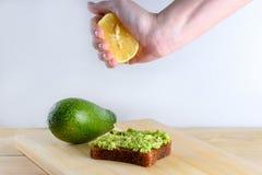 Frauenhand, die halb von der Zitrone auf Avocadotoast des ganzen Brotes zusammendr?ckt stockfotografie