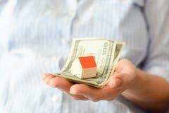 Frauenhand, die Haus halten und Geld, welches die steigenden Kosten von Inlandspreisen vorschlägt Stockbilder