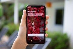 Frauenhand, die iPhone X mit APP-Haus auf Schirm hält Stockfotografie