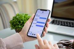 Frauenhand, die iPhone X mit Social Networking-Service iMes hält lizenzfreie stockfotografie