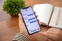 Frauenhand, die iPhone X mit Social Networking-Service iMess hält stockfotografie