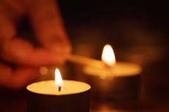 Frauenhand, die Kerze einstellt Stockbild