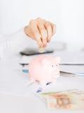 Frauenhand, die Münze in kleines Sparschwein setzt Lizenzfreie Stockbilder