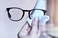 Frauenhand, die modische schwarze Glaslinse mit weißem microfiber Gewebe säubert Bewirken Sie seitlichen 50mm Nikkor Lizenzfreie Stockfotos