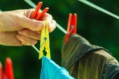 Frauenhand, die nasse Kleidung auf Seillinie hängt Stockbild