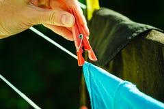 Frauenhand, die nasse Kleidung auf Seillinie hängt Lizenzfreie Stockbilder