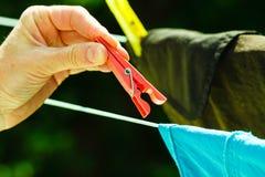 Frauenhand, die nasse Kleidung auf Seillinie hängt Stockfoto
