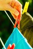 Frauenhand, die nasse Kleidung auf Seillinie hängt Stockfotografie