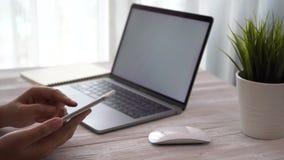 Frauenhand, die online auf Laptop und Smartphone und Arbeiten kauft stock footage