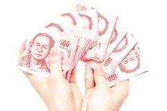 Frauenhand, die Satz der Banknote des thailändischen Baht 100 zählt Stockfoto