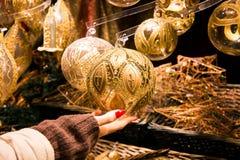 Frauenhand, die schön in Handarbeit gemachten Weihnachtsdekorationsball in der Goldfarbe mit dekorativem Entwurf hält lizenzfreie stockbilder