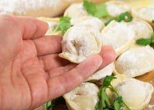 Frauenhand, die selbst gemachte ungekochte Ravioli hält Stockbilder