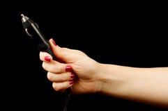 Frauenhand, die Selbstfeuerzeugverbindungsstück auf dem schwarzen Hintergrund hält Lizenzfreie Stockbilder