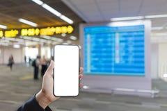 Frauenhand, die Smartphonemodell und unscharfen Flugplanhintergrund hält stockfoto