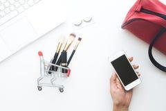 Frauenhand, die tragbares Gerät mit Warenkorb- und Kosmetikeinzelteilen und Laptop auf weißem Hintergrund, Draufsichton-line-Eink Stockbild