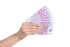 Frauenhand, die viele fünfhundert Eurobanknoten zahlt Stockfotografie