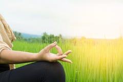Frauenhand, die Yoga und Meditation über Naturgrünfeld tut Lizenzfreies Stockfoto