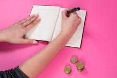 Frauenhand hält einen Stift in der Hand und schrieb nahe bei der Münze auf rosa Hintergrund stockfotografie