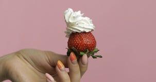 Frauenhand hält Erdbeere mit Schlagsahne auf die Beere stockfoto