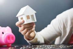 Frauenhand hält Hausmodell lizenzfreies stockfoto