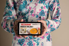 Frauenhand halten beweglich mit dem Bestellungslebensmittel on-line stockbild