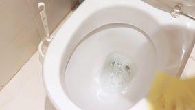 Frauenhand im gelben Gummihandschuh, der eine schmutzige Toilettenschüssel säubert stock footage